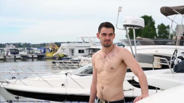 ein junger mann in jeans auf einem boot steht, schaut in die ferne und das lächeln - nackter oberkörper stock-videos und b-roll-filmmaterial