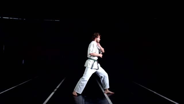 junger mann in kimono, durchführung karate bogen vor dem üben. schwarzer hintergrund - sportchampion stock-videos und b-roll-filmmaterial