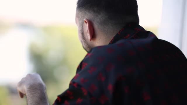 기모노를 입은 젊은 남자가 이른 아침에 발코니에 서서 눈을 비비다. - 한 명의 중년 남자만 스톡 비디오 및 b-롤 화면