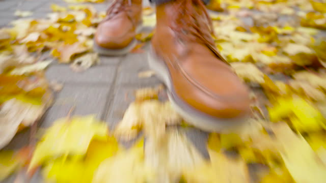 A young man in leather shoes is walking along a path with fallen leaves.
