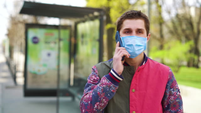 Young man in medical mask talking on phone on bus stop Young man wearing medical mask standing on bus stop and talking on phone, cars and pedestrians passing by. Portrait of guy ordering taxi during COVID outbreak. Concept of pandemic bus stop stock videos & royalty-free footage