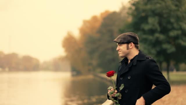 Jovem no parque, cheirando uma rosa, amor - vídeo