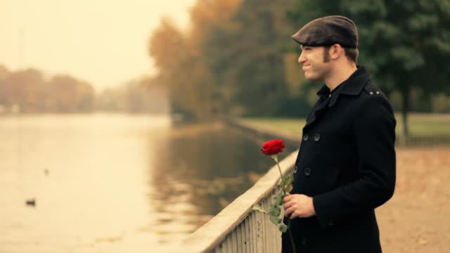 Jovem no parque, cheirando uma rosa, amantes - vídeo