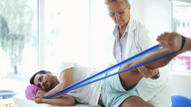 junger mann in der physikalischen therapie. - hüfte stock-videos und b-roll-filmmaterial