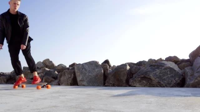 Junger Mann in rote Turnschuhe Rochen am Meer – Video