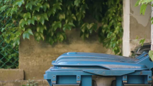 young man in red sportswear throwing away rubbish - coperchio video stock e b–roll