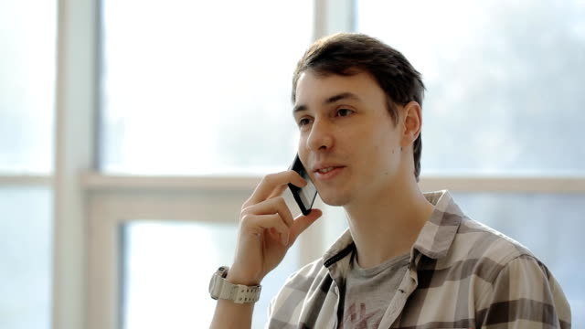 Young man in shirt smiling and talking on smartphone in a bright room with windows video