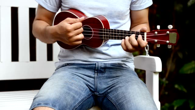 Young man in short blue jeans and blue tshirt playing small travel guitar. video