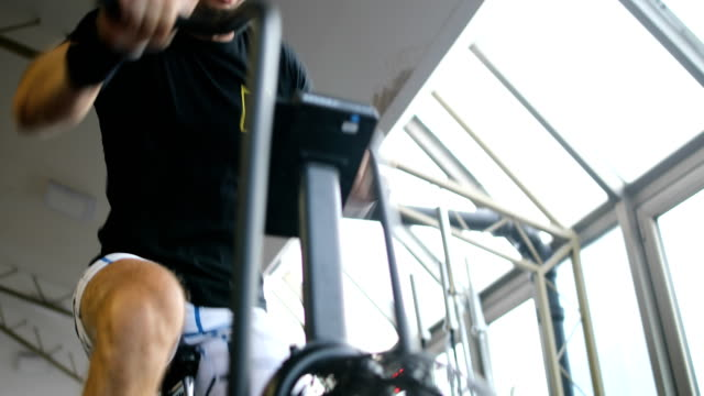 young man in sports shoes cycling at gym - evento ciclistico video stock e b–roll