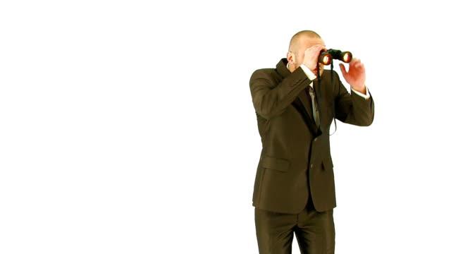 Young man in suit looking through binoculars. Medium Plan