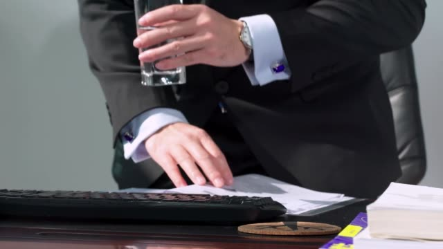 Young man in suit sitting on office chair and reading documents in front of the computer, drinks water for hydration.Get up from the chair