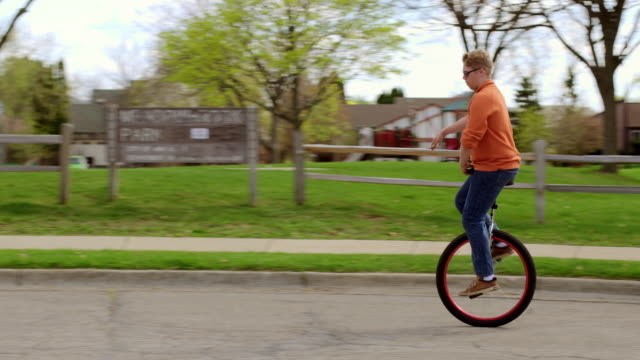 Young man in sunglasses rides unicycle in suburbia video