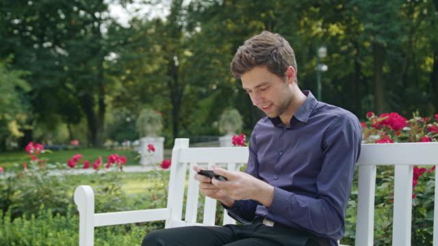 携帯電話を使用してゲームをプレイする公園の若い男 - ベンチ点の映像素材/bロール