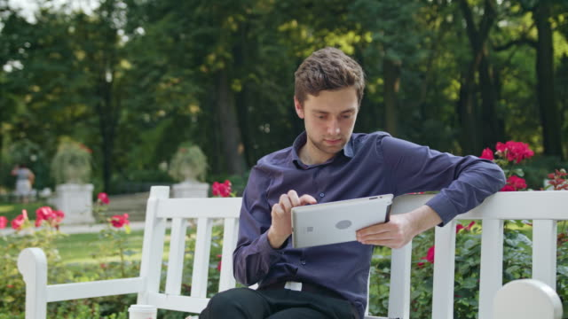 Young Man in the Park Using a Tablet video
