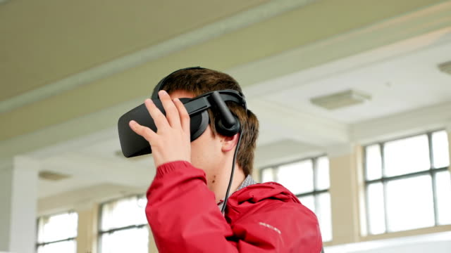 Young man in VR headset playing virtual game video