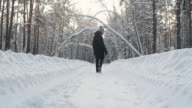 istock young man in warm winter clothes walks through the winter snow forest. 1204227776