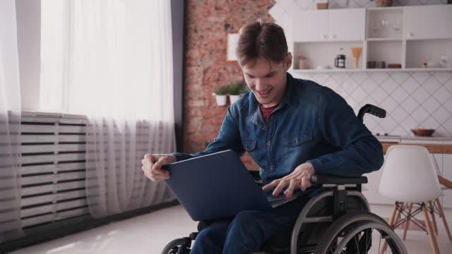 ung man i rullstol använda laptop eller modern dator hemma - fysiskt funktionshinder bildbanksvideor och videomaterial från bakom kulisserna