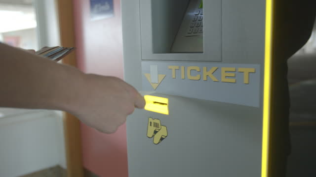 Young man inserts car park ticket into ticket machine, detail video