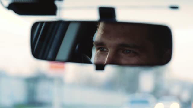 vídeos de stock e filmes b-roll de young man inside car. happy positive caucasian man driving car fast and look at rear view mirror with smile. blurred background. slow motion. - espelho