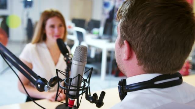 vidéos et rushes de jeune homme, interviewant un invité en studio pour un podcast - podcasting