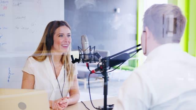 vídeos de stock, filmes e b-roll de jovem, entrevistando um convidado em um estúdio para um podcast - podcast