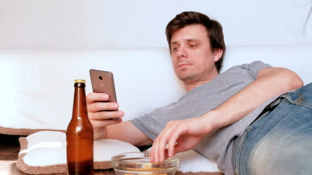 Young man is browsing internet in his mobile phone, eating chips and drinking beer laying on the floor. Young man is browsing in her mobile phone, eating chips and drinking beer laying on the floor onion ring stock videos & royalty-free footage