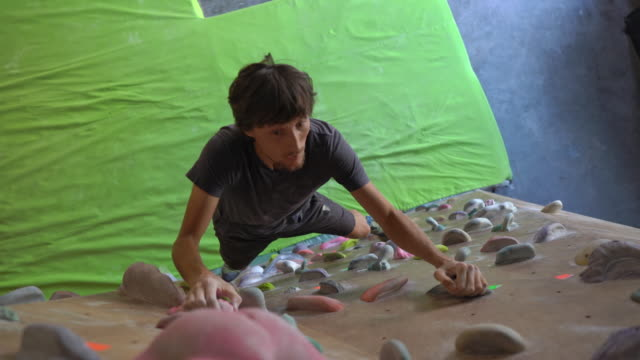 Young man is climbing the wall in a bouldering climbing gym Young man is climbing the wall in a bouldering climbing gym. boulder rock stock videos & royalty-free footage