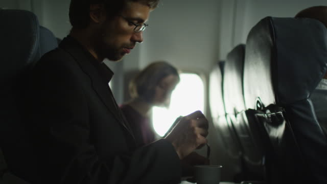 Young man is drinking coffee on an airplane and a woman is reading in the background next to a window. video