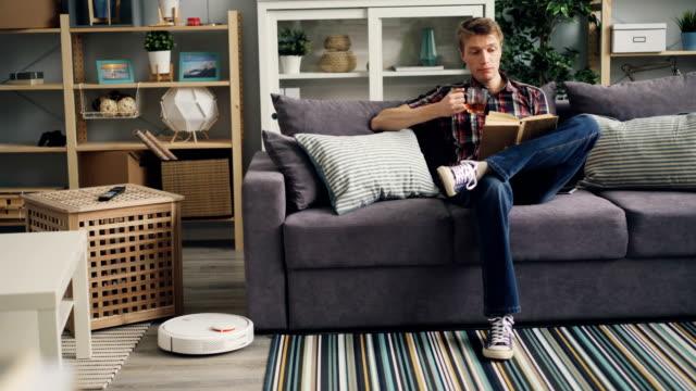 若い男は、ロボット掃除機が自宅で床に取り組んでいる間、ソファの上に座ってお茶や読書本を飲んでいる - 電化製品点の映像素材/bロール