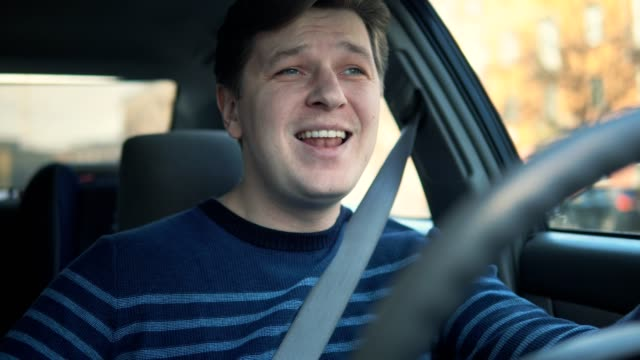 a young man is driving a car and singing - śpiewać filmów i materiałów b-roll