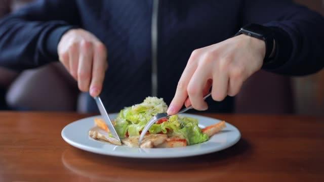 vidéos et rushes de un jeune homme mange une délicieuse salade de poulet - fourchette