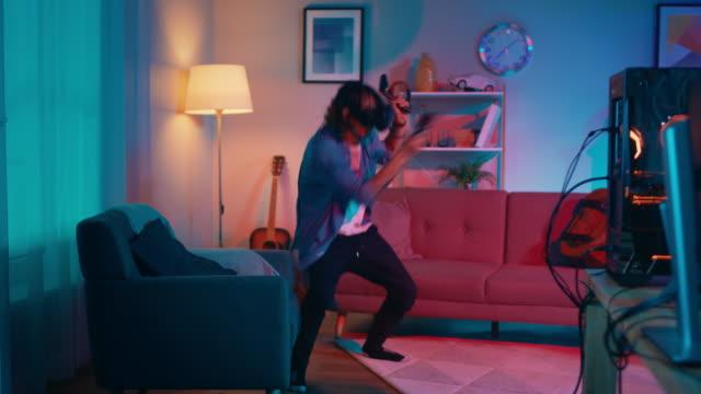 jüngling ist energetisch eine virtuelle realität videospiel während tragen einen kopfhörer zu spielen. er steht in einem gemütlichen zimmer mit warmen neonlichter. er ist swingen hände, schießen und ausweichen von hindernissen. - computerspieler stock-videos und b-roll-filmmaterial