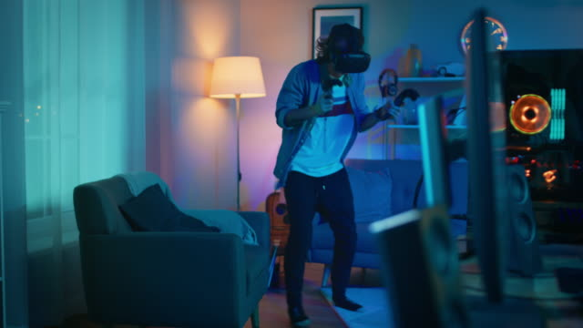 Young Man is Energetically Playing a Virtual Reality Video Game While Wearing a Headset. He's is Standing in a Cozy Room with Warm Neon Lights. He's Swinging Hands, Shooting and Dodging Obstacles. Young Man is Energetically Playing a Virtual Reality Video Game While Wearing a Headset. He's is Standing in a Cozy Room with Warm Neon Lights. He's Swinging Hands, Shooting and Dodging Obstacles. Shot on RED EPIC-W 8K Helium Cinema Camera. video game stock videos & royalty-free footage