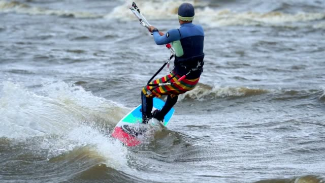 SLOW MOTION: A young man is engaged in kiting. He beautifully skates on the board on the waves of the pond. Strong wind blows. Man loves kiting in extreme weather. Cold autumn weather video