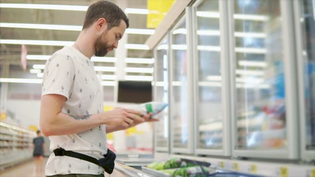 young man is examining pack with frozen vegetables in a hall of supermarket - vegan stock videos and b-roll footage