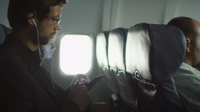Young man is listening to music on an airplane and a woman is using tablet in the background next to a window. video