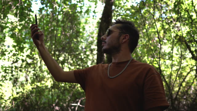 Young man is looking for a cellular network in woods. video