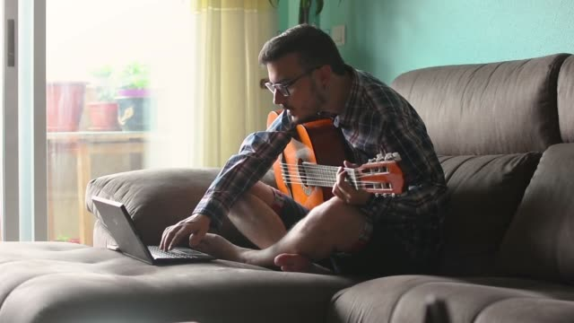 vídeos de stock e filmes b-roll de young man is playing guitar in the couch of his house - instrumental