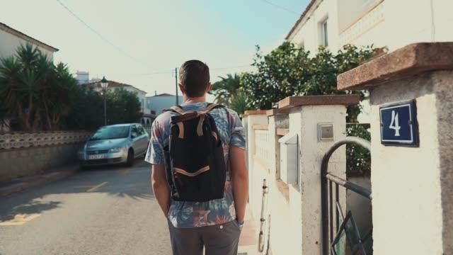 ung man strosa längs staket av små stugor i city i sommardag - mellanöstern bildbanksvideor och videomaterial från bakom kulisserna