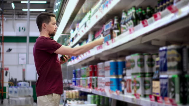young man is taking beer bottles from shelf in supermarket in aisle - vídeo
