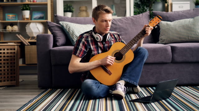 Young man is watching tutorial using laptop and playing the guitar sitting on floor at home Young man in casual clothing is watching tutorial using laptop and playing the guitar sitting on floor at home learning to use musical instrument. Youth, fun and internet concept. guitar stock videos & royalty-free footage