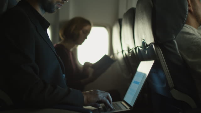 Young man is working on a laptop on an airplane and a woman is reading in the background next to a window. video