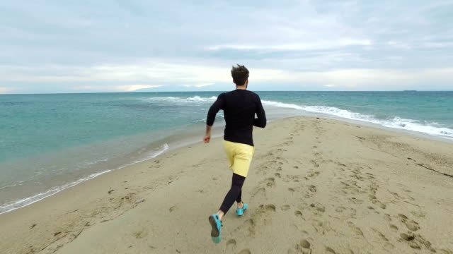 Young man jogging at the beach video