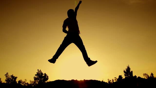 ZEITLUPE: Junger Mann springen bei Sonnenuntergang – Video