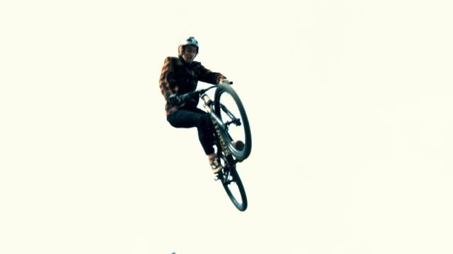 MS Young man jumping BMX bicycle above ramp