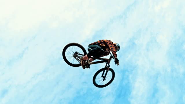 vidéos et rushes de mme young man saut vélo bmx contre le ciel bleu et nuages - vue en contre plongée