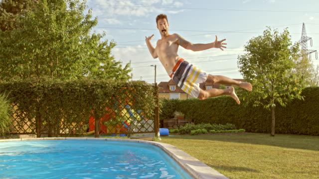rallent ts giovane uomo saltare in piscina - saltare video stock e b–roll