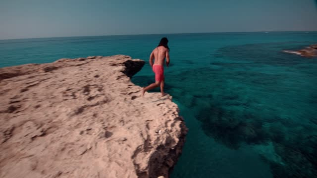 Young man jumping off cliff and diving into sea Young adventurous diver jumping off cliff and diving into tropical island blue sea water cliff jumping stock videos & royalty-free footage