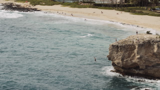 Young man jumping off cliff into ocean Aerial view of young caucasian man jumping off cliff into ocean cliff jumping stock videos & royalty-free footage