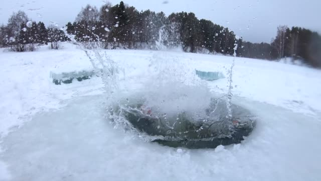 young man jumps into the ice hole - foro video stock e b–roll